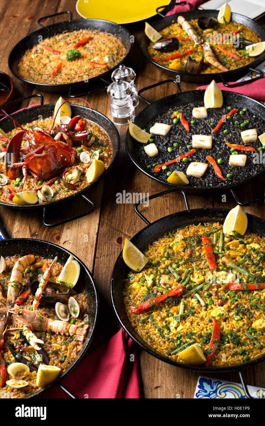 Black pans of fried lobster, mantis prawn, shrimps, clams and crabs with lemon, chili and herbs on wooden table - Stock Image