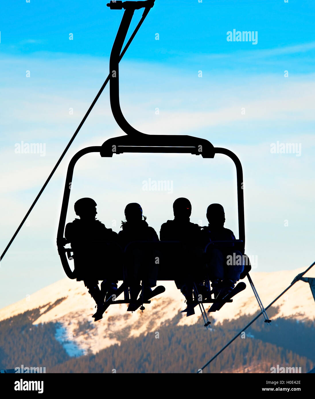 Silhouette of a group of people on a ski lift at ski resort. - Stock Image