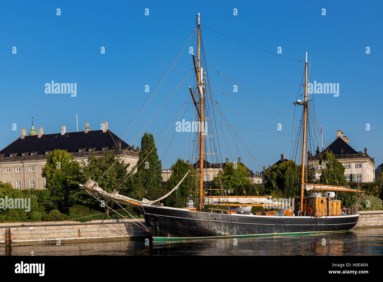 Old wooden sail ship at dock near Amalienborg Palace, Copenhagen, Denmark - Stock Image