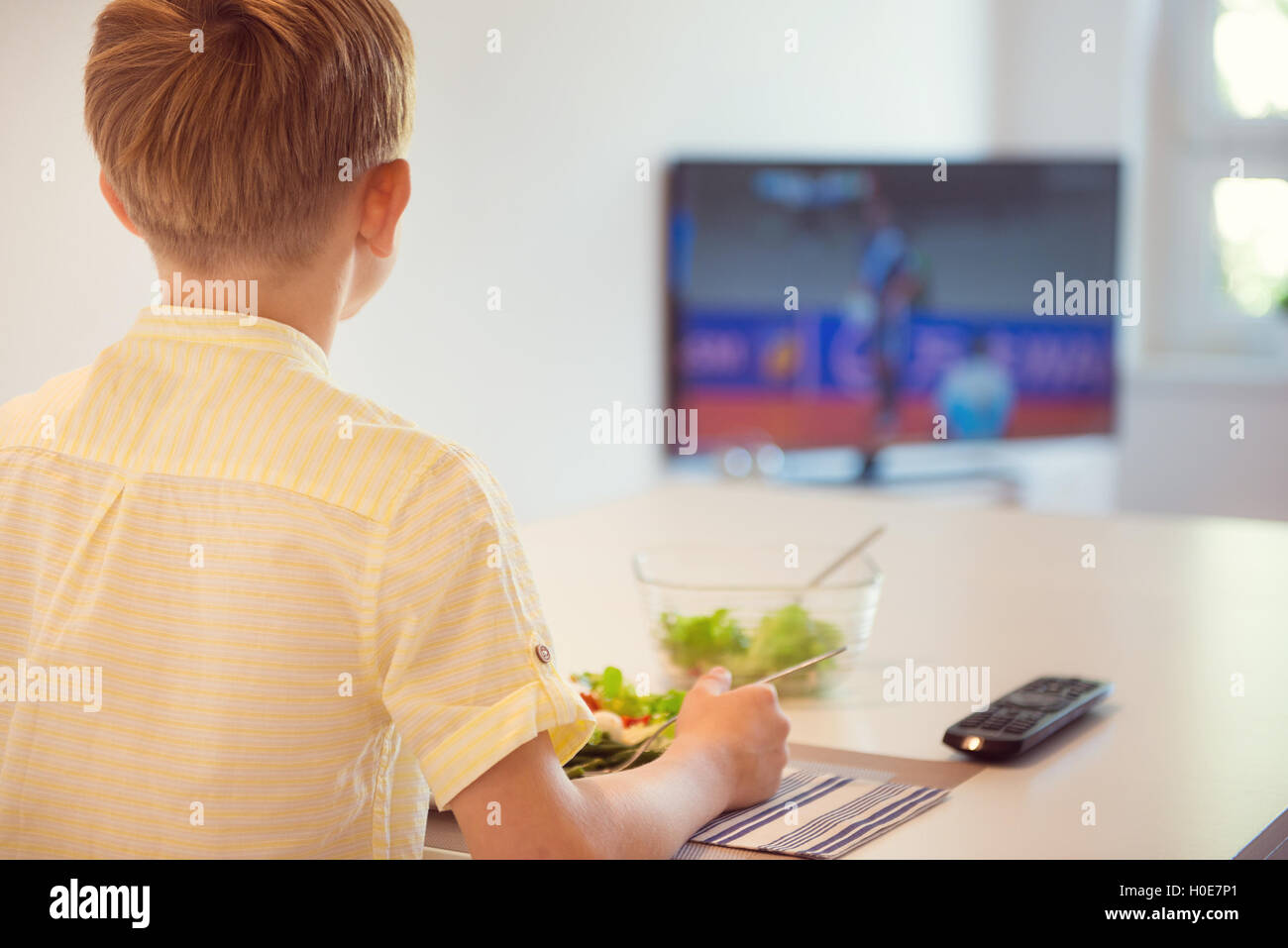 Cute boy child eating at the table in kitchen and watching football - Stock Image