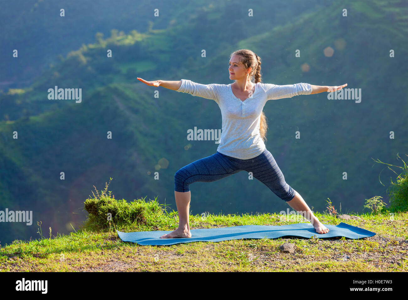 Woman doing yoga asana Virabhadrasana 2 - Warrior pose outdoors - Stock Image