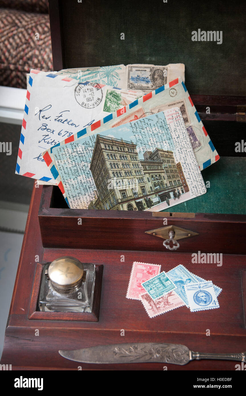 Vintage letters, stamps inkwell and letter opener in an antique writing box - Stock Image