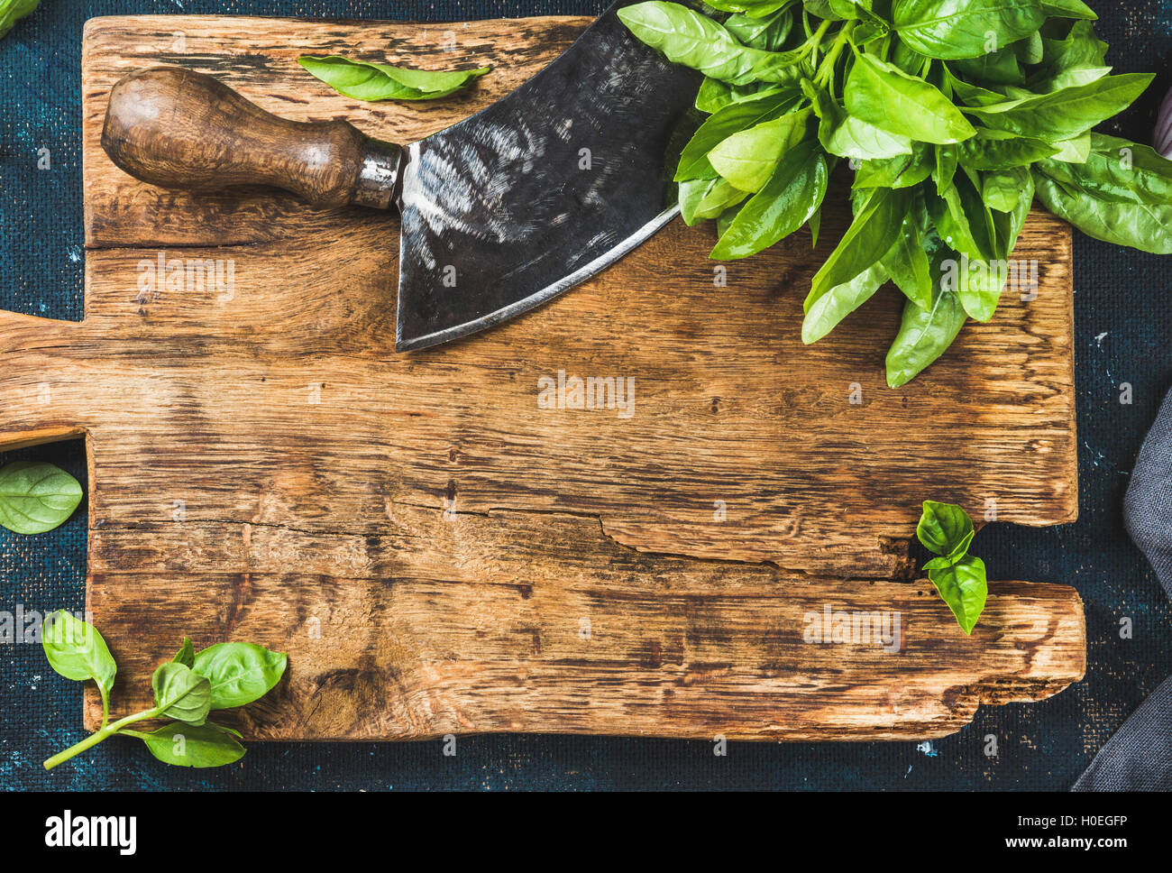 Fresh green basil and vintage herb chopper on rustic wooden bord, top view, copy space, horizontal composition - Stock Image