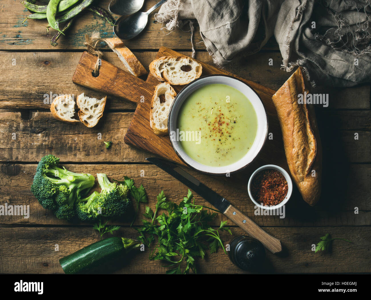 Homemade pea, broccoli, zucchini cream soup in white bowl with fresh baguette on wooden board over rustic background, - Stock Image