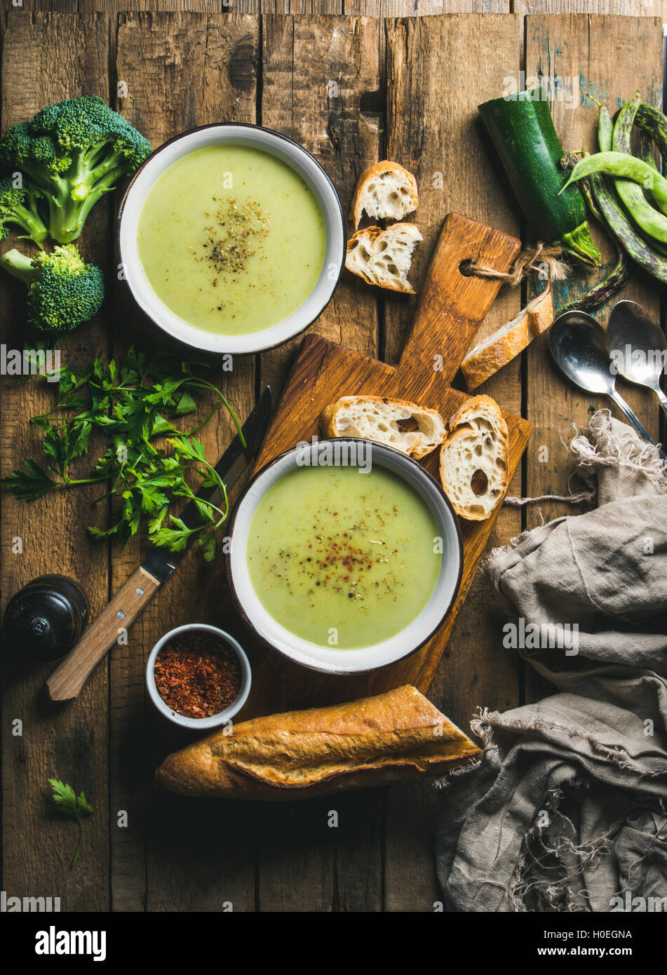 Two bowls of homemade pea, broccoli and zucchini cream soup served with fresh baguette and vegetables on wooden - Stock Image