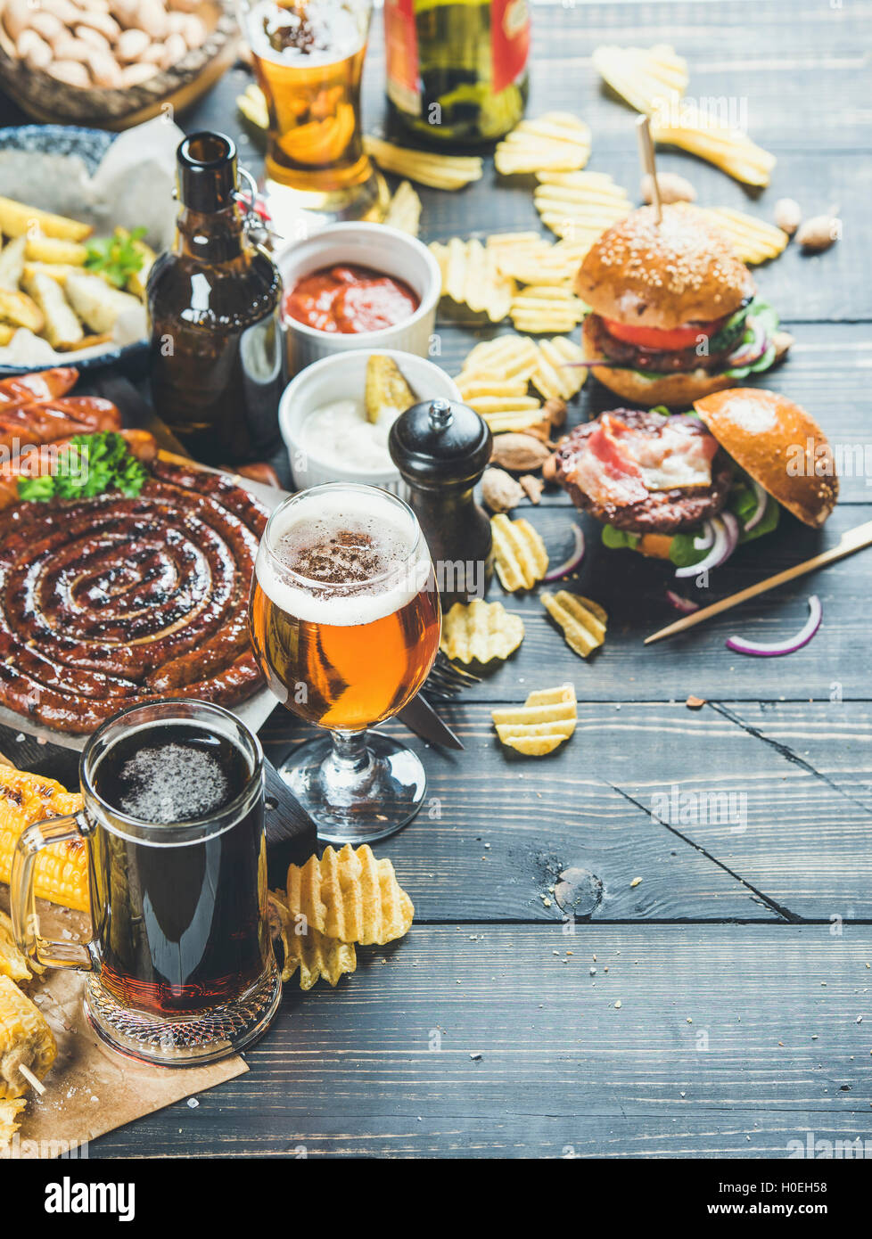 Beer and snack set. Octoberfest food frame concept. Beers assortment, grilled sausages, burgers, fried potato, corn, - Stock Image