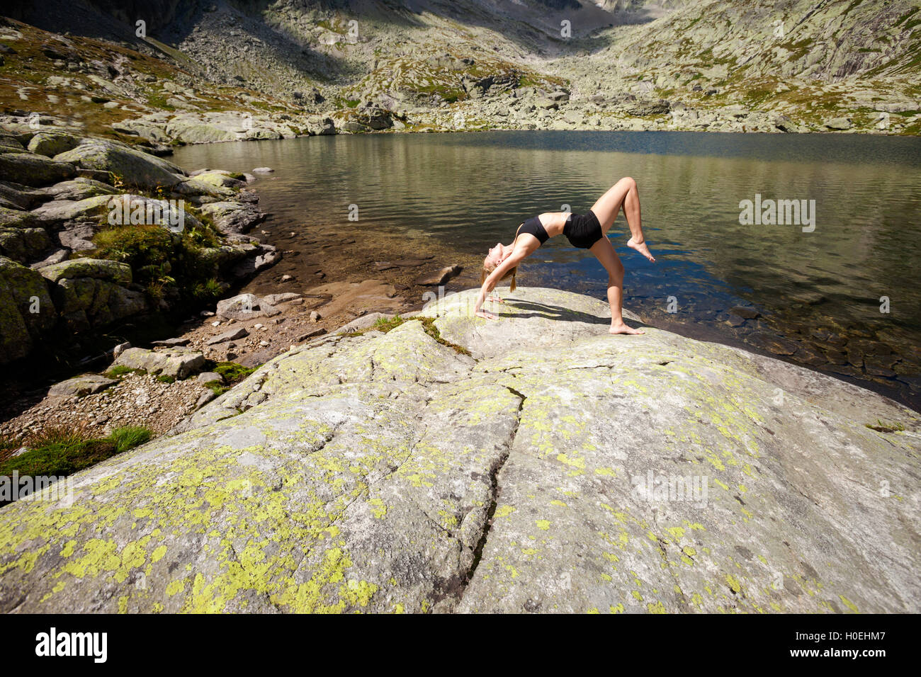 Exercise yoga everywhere - in slovakian Tatry mountains. Beautiful panorama - Chata Teryho, kotlina Piatich Spisskych - Stock Image