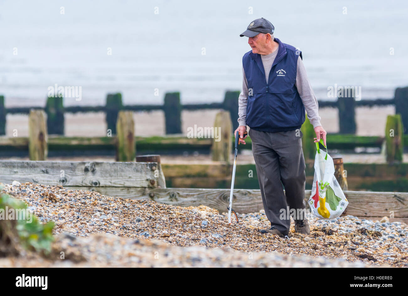 Elderly man picking up litter from a beach. - Stock Image