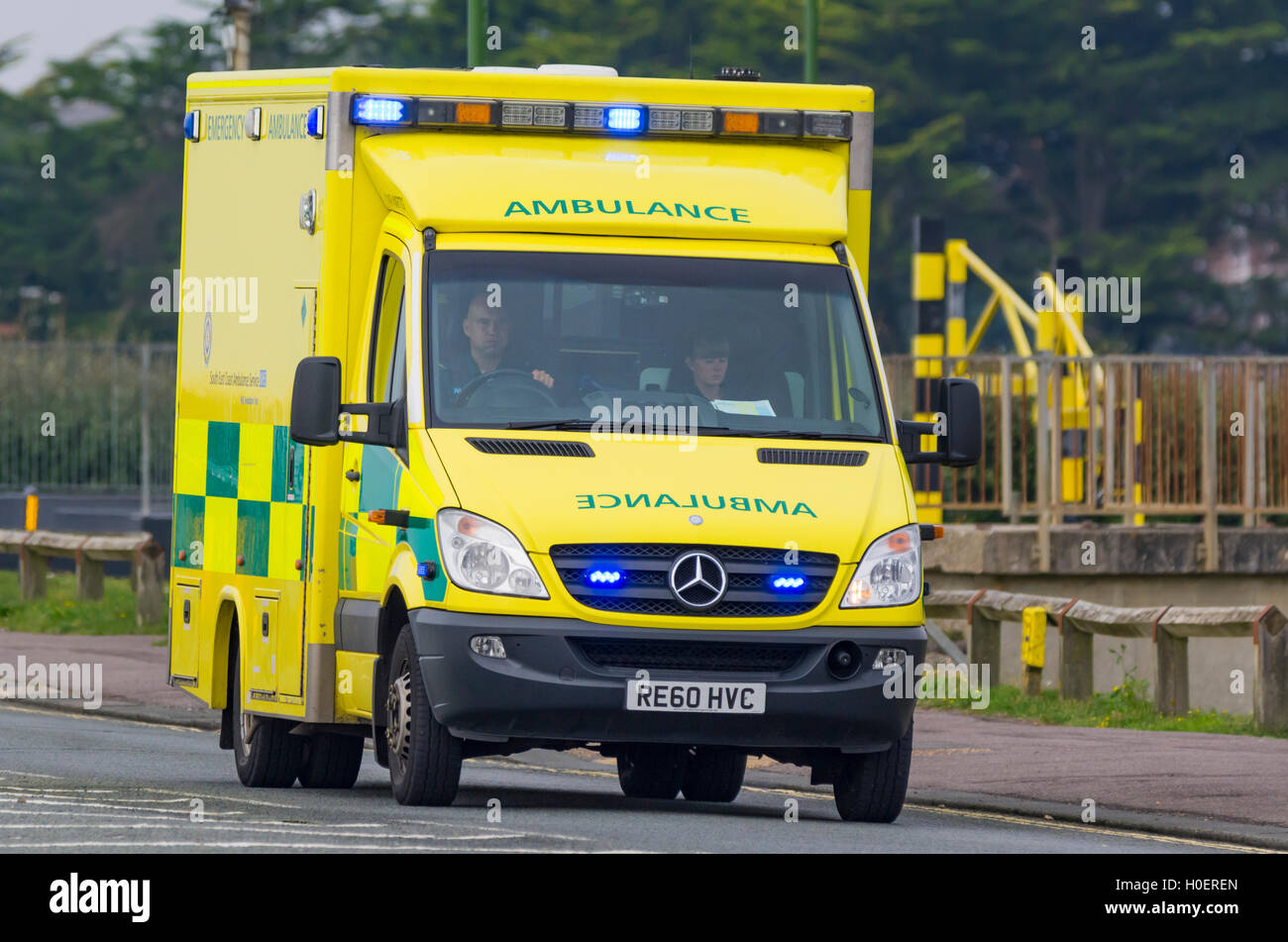 Ambulance with blue lights flashing on a road in the UK. NHS ambulance UK. Ambulance blue lights. Ambulance service. - Stock Image