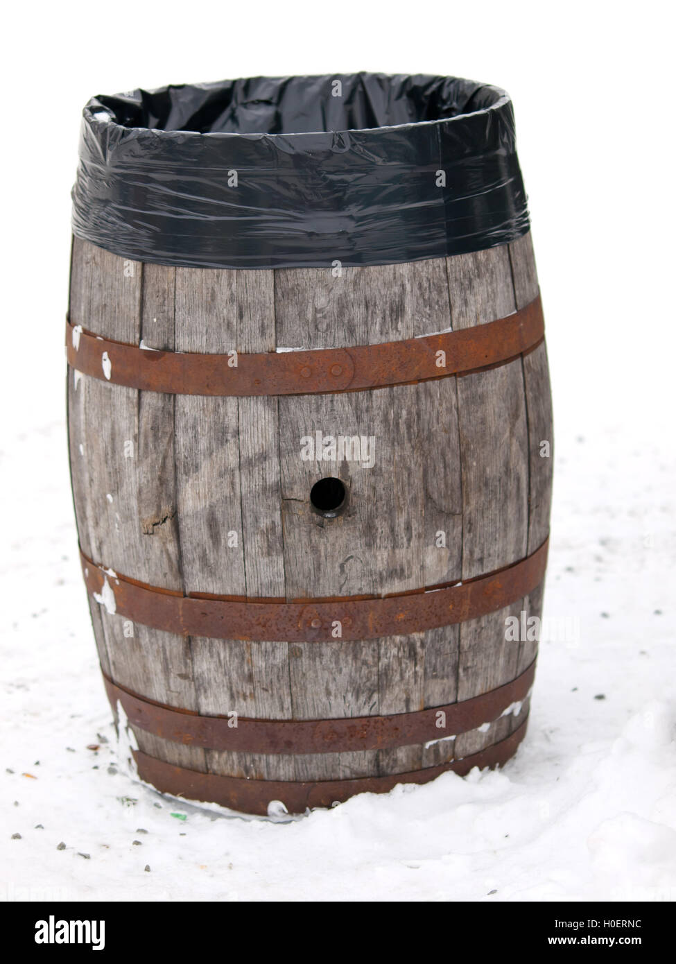 Old wooden baril reused as garbage container in ski resort - Stock Image