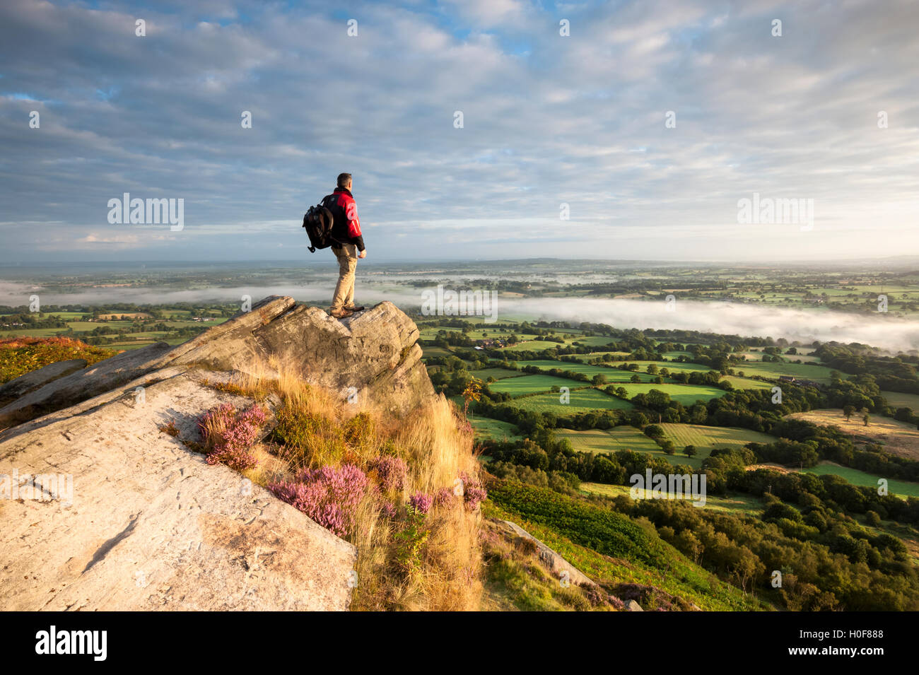 A rambler looking across the Cheshire plains with cloud inversion from Cloudside near Congleton, Cheshire. Stock Photo
