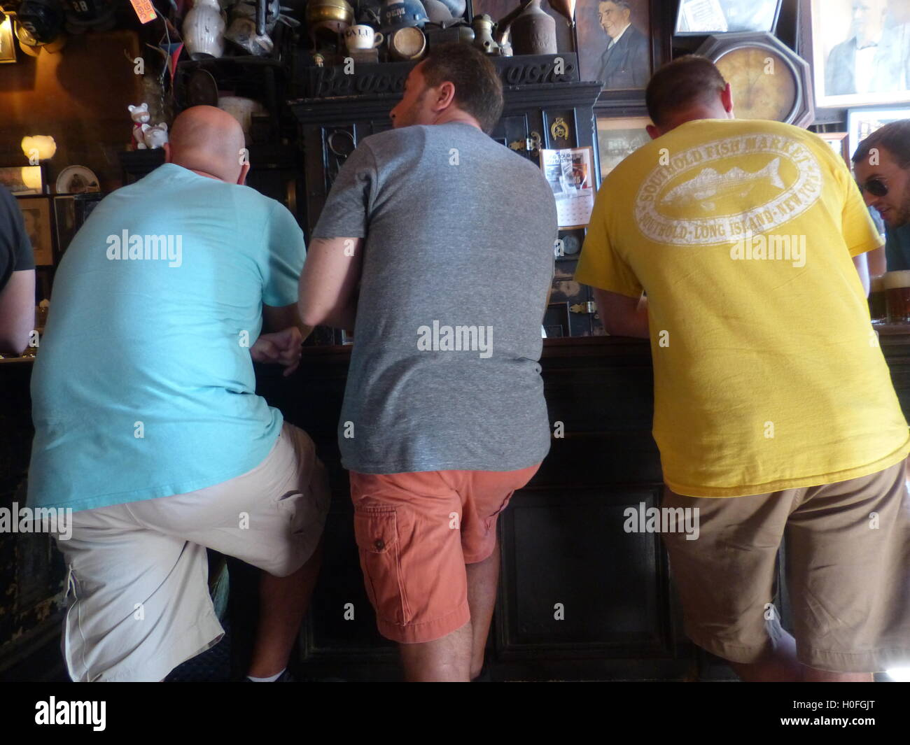 Guests in colorful shirts lean over bar while drinking beer - Stock Image