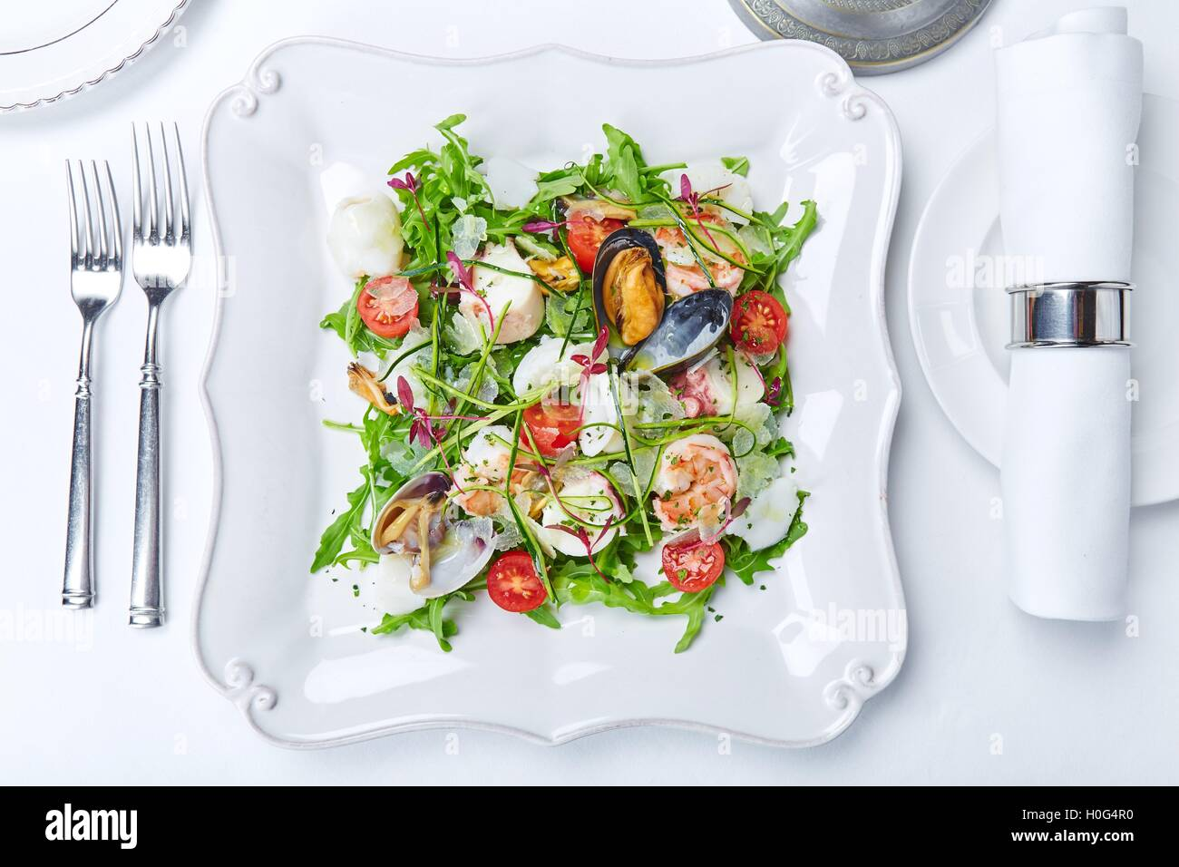 Seafood salad with clams, shrimps, squid, lettuce, tomatoes and herbs on white plate Stock Photo