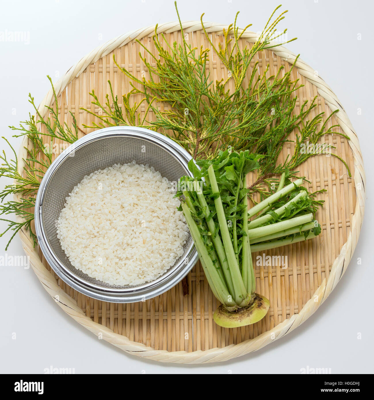 Rice with white radish leaves and herbs on bamboo tray Stock Photo