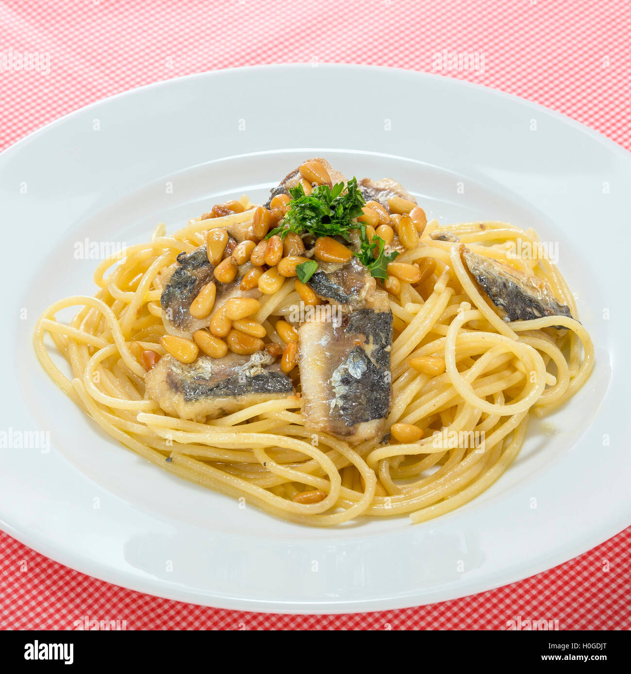 Noodle pasta with sardine fish on white platter - Stock Image