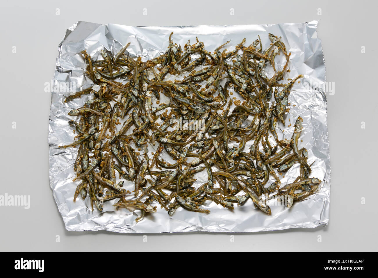 Fried dried anchovy fish on aluminum paper in asia - Stock Image
