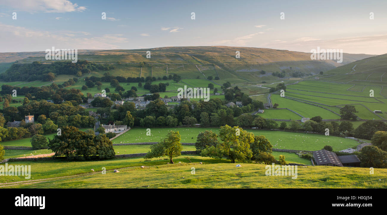 Summer evening view over picturesque Dales village of Arncliffe (church & houses) nestling in valley under sunlit hills - North Yorkshire, England, UK Stock Photo
