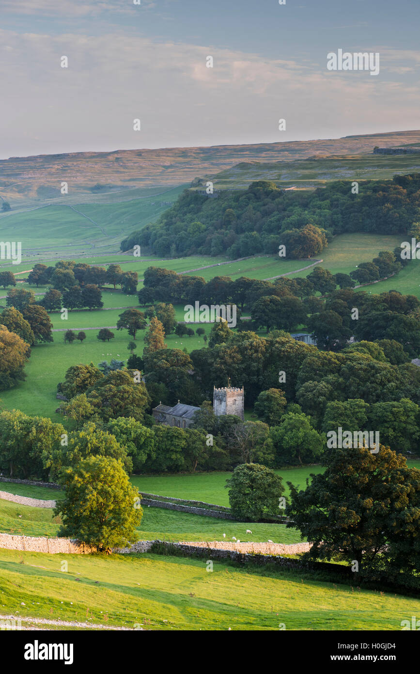 Summer evening view over church (& tower) in picturesque Dales village nestling in valley under sunlit hills - Arncliffe, North Yorkshire, England, UK Stock Photo