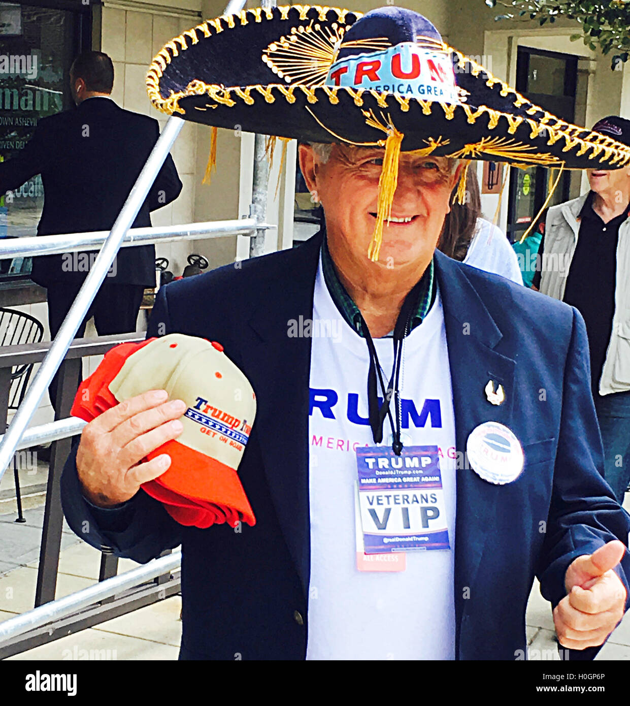 A Donald Trump supporter attends a Trump rally in Asheville, NC wearing a Sombrero with a Trump sticker holding - Stock Image