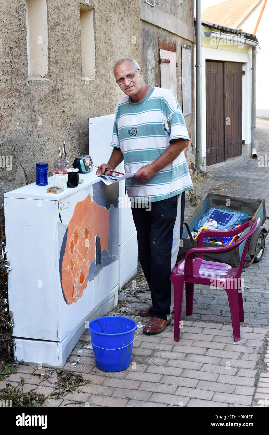 Harald Muller paints a junction box in Kalbe/Milde, Germany, 13 September 2016. The city is evolving into a cente - Stock Image