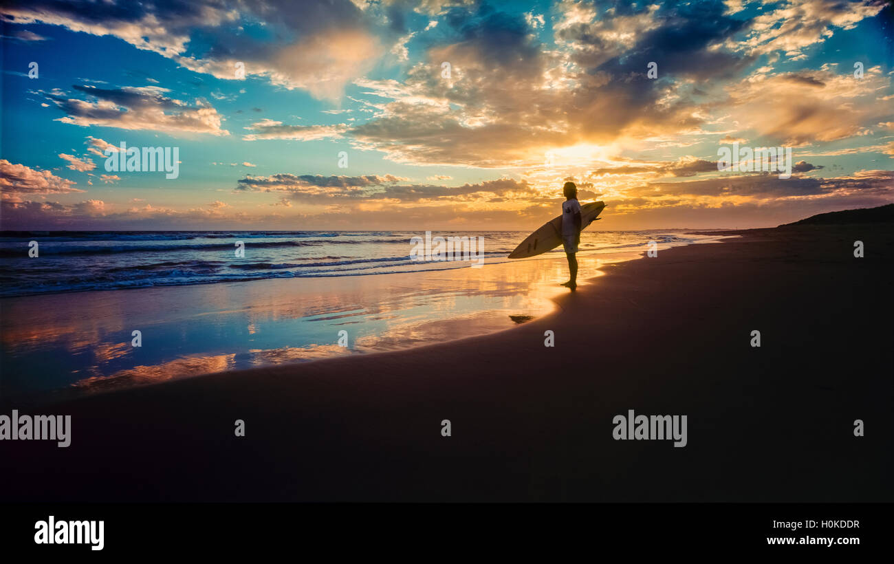 Silhouette of surfer on beach holding surfboard at sunrise or sunset - Stock Image