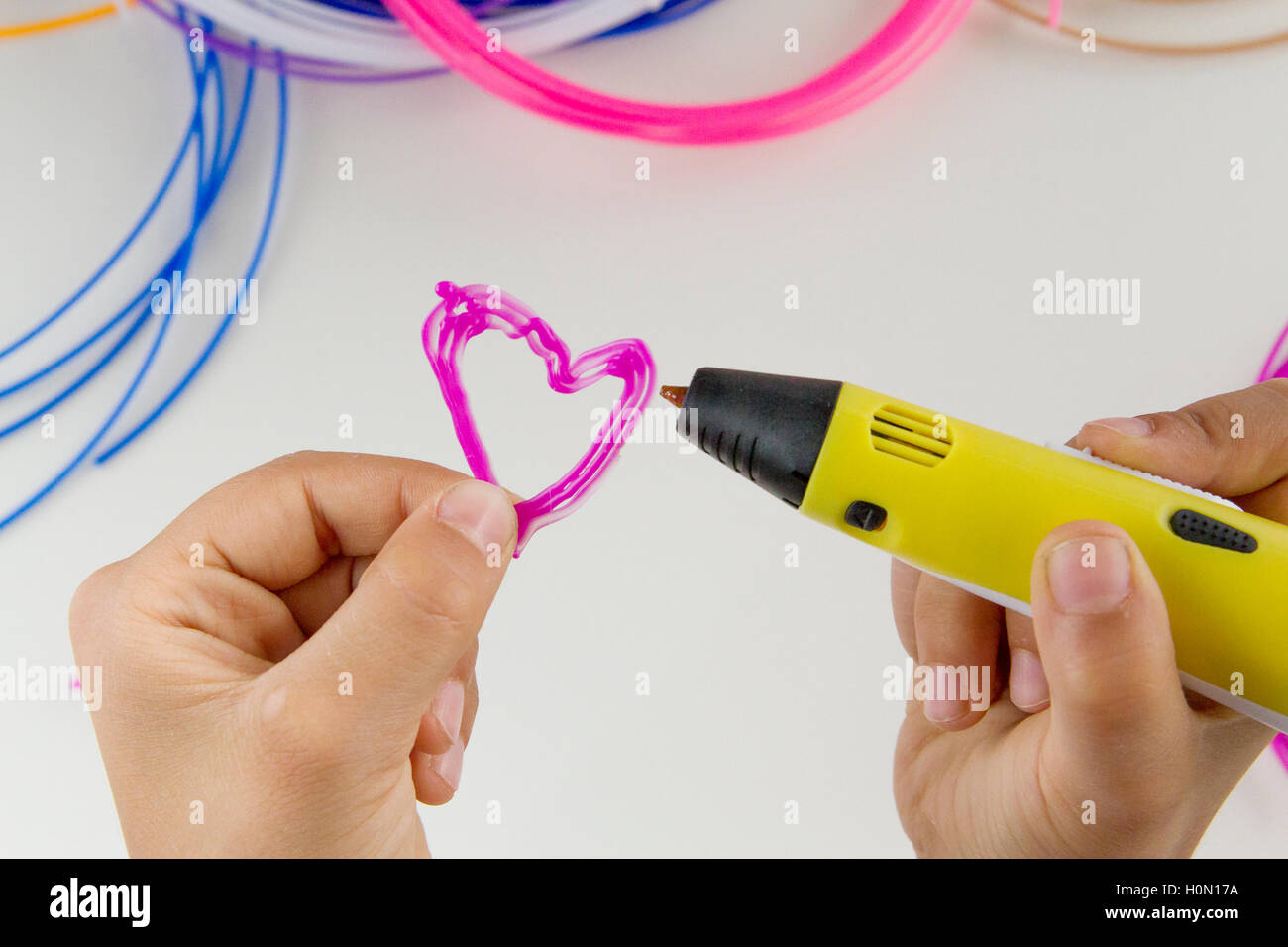 Child makes with 3d drawing pen a heart. Colourful filaments and white background. Top view. Close up - Stock Image