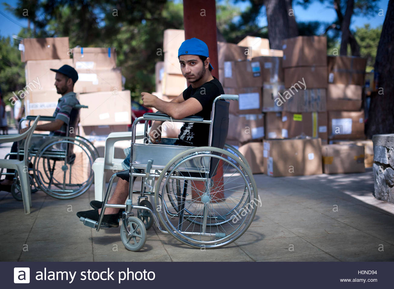 A disabled refugee at PIKPA refugee center, Lesbos, Greece. - Stock Image