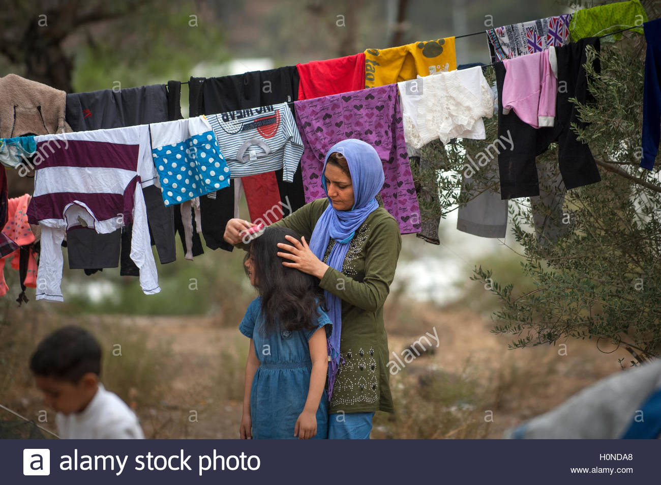 A refugee mother combs her daughter's hair at Moria Refugee Camp, Lesbos, Greece. - Stock Image