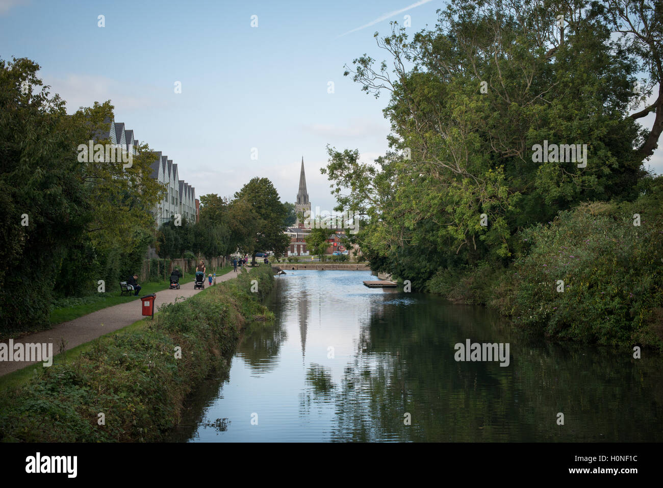 People walk along the towpath next to Chichester Canal in Chichester, West Sussex. - Stock Image