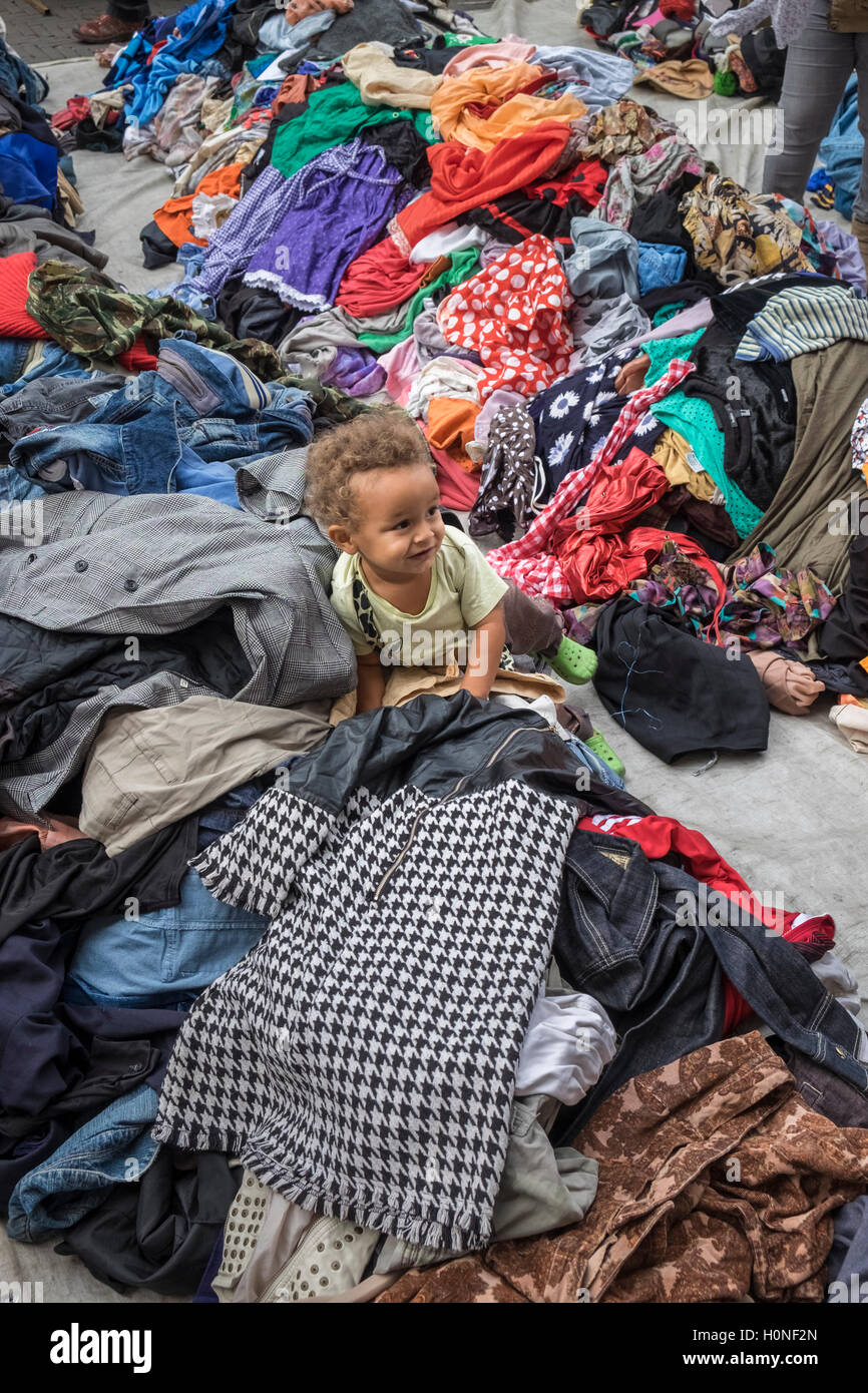 Young child playing among colourful clothing at Waterlooplein Street Market, Amsterdam, Netherlands - Stock Image