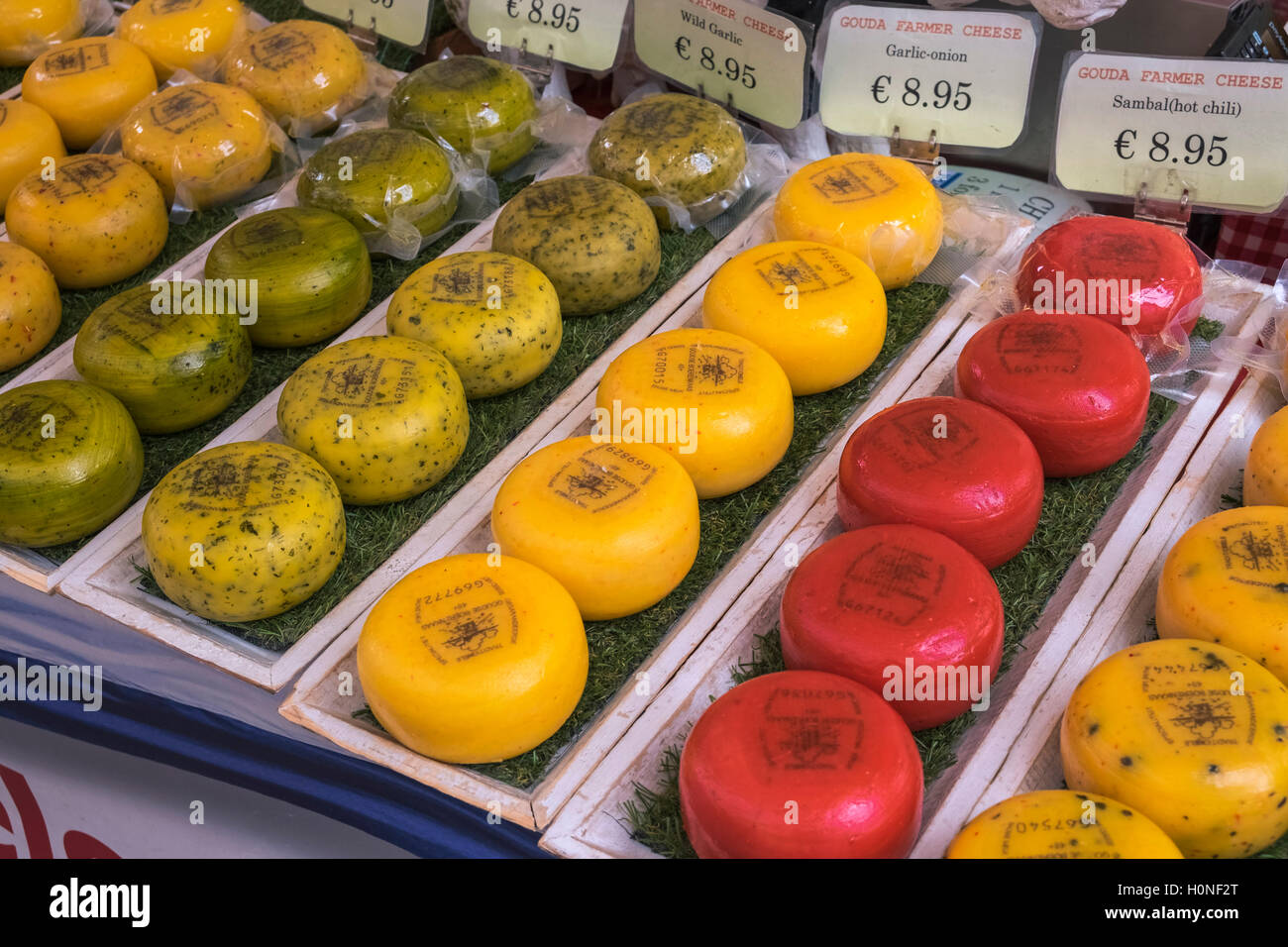 Colourful Dutch Gouda cheese displayed on a market stall, Waterloopleinmarkt, Amsterdam, Netherlands - Stock Image
