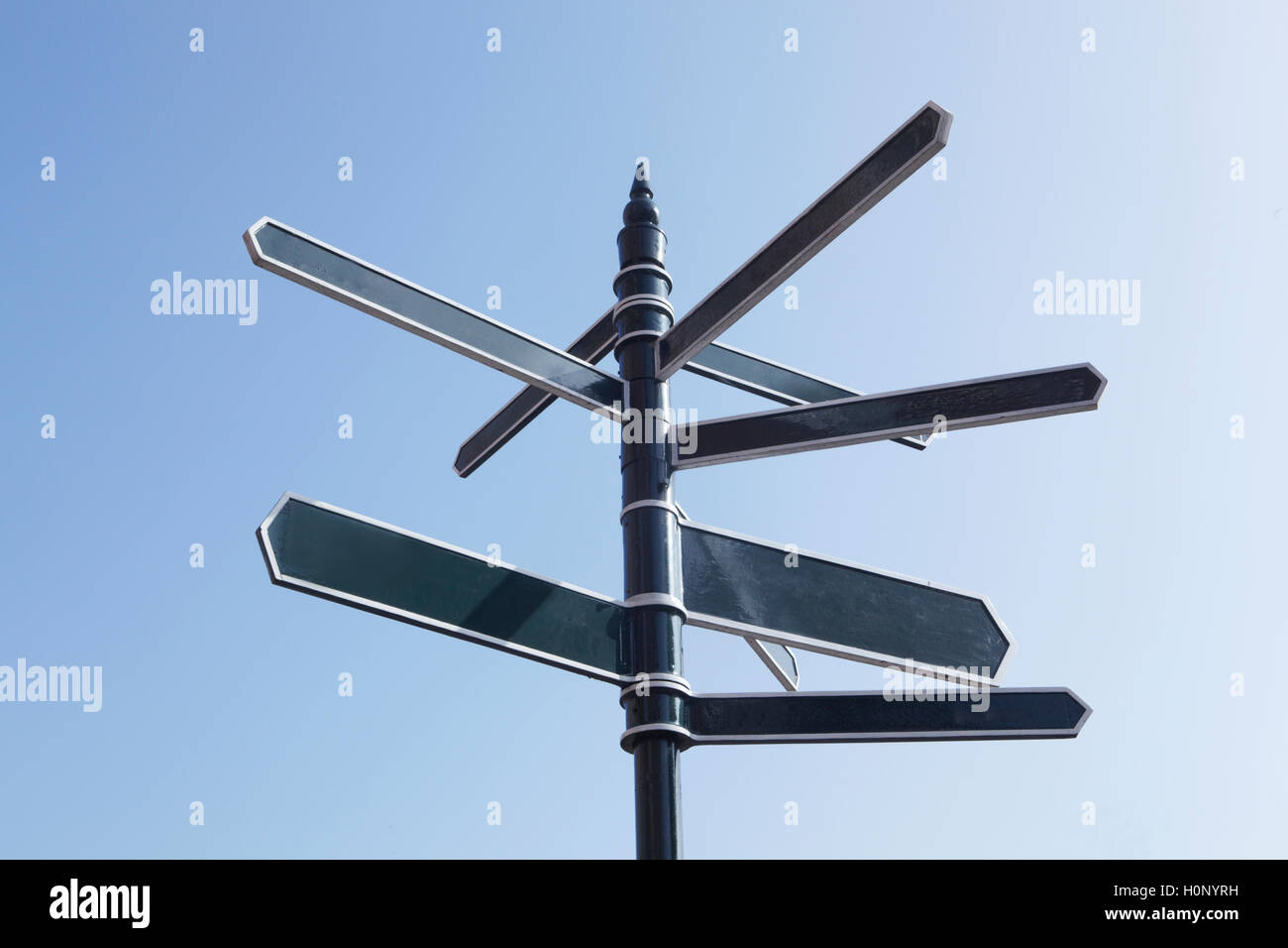 Signpost Pointing In Many Directions Against Blue Sky - Stock Image