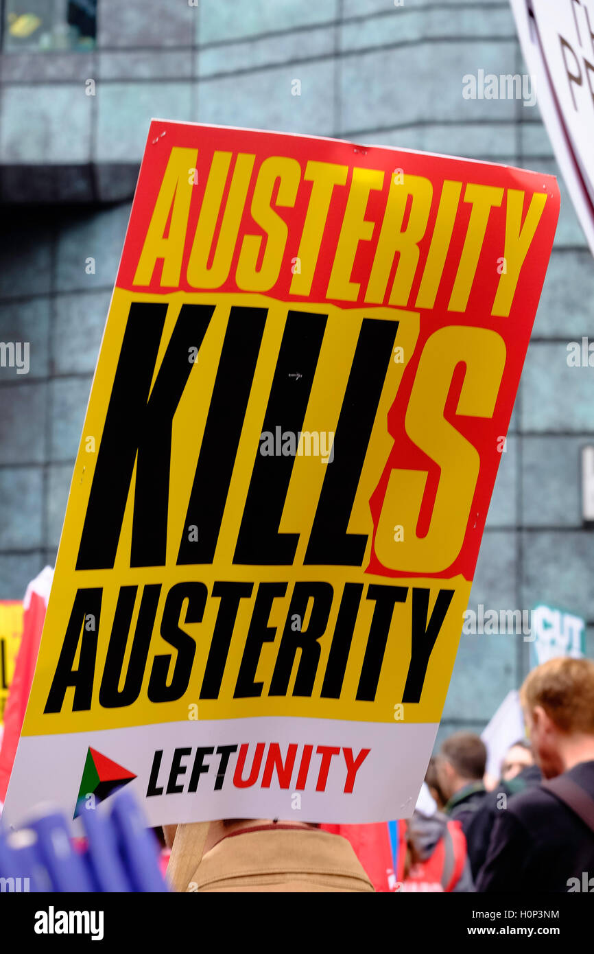 brightly colored 'Austerity kills' placard held by protestor at anti-austerity march in London - Stock Image