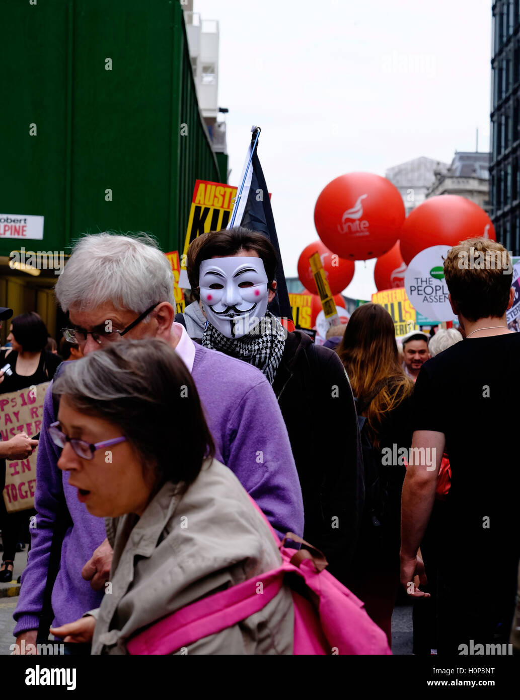Protestor wearing Guy Fawkes mask at anti-austerity protest in London, England - Stock Image