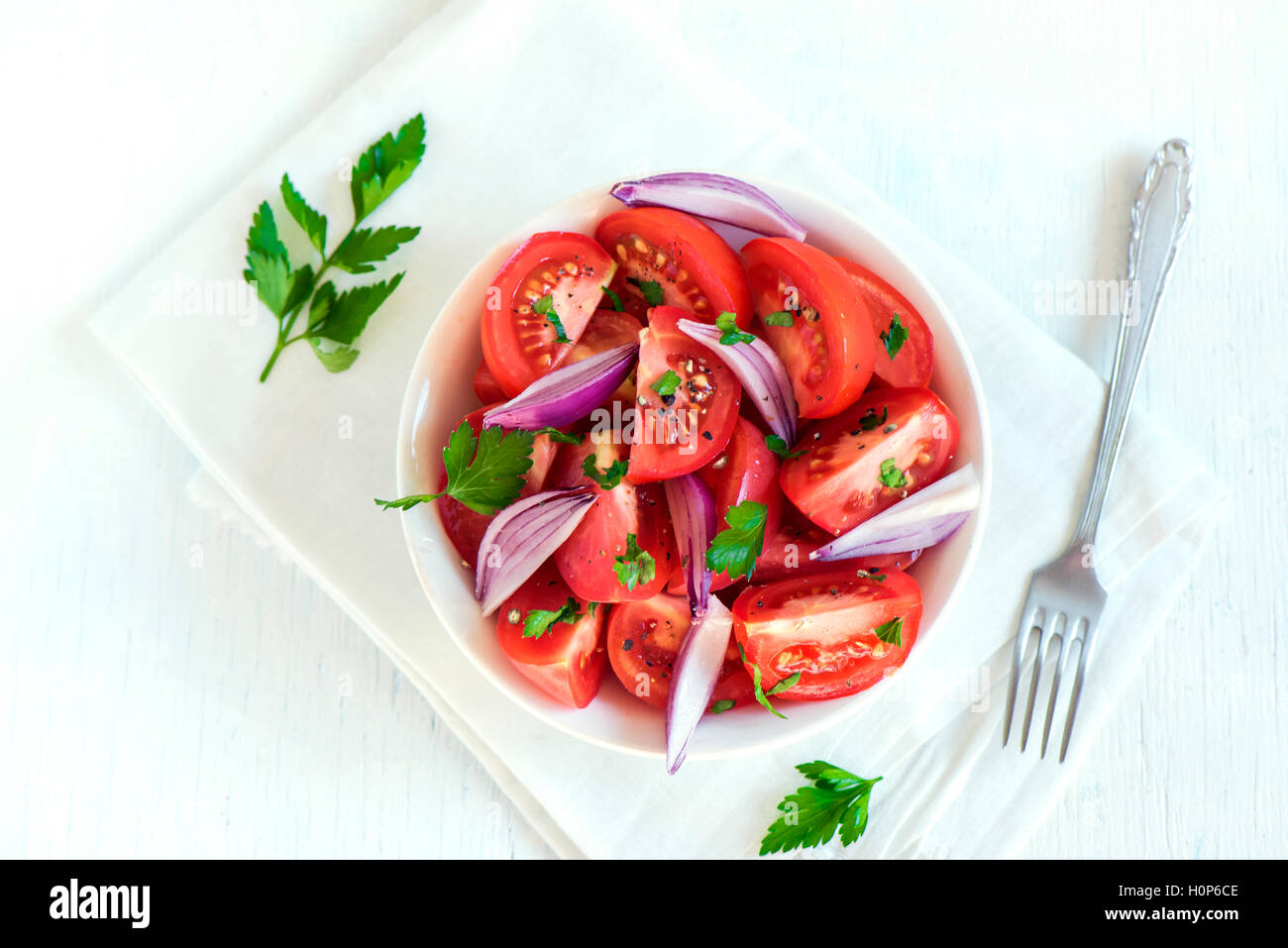 Tomato salad with onion, parsley and black pepper in bowl - healthy vegetarian vegan food appetizer - Stock Image