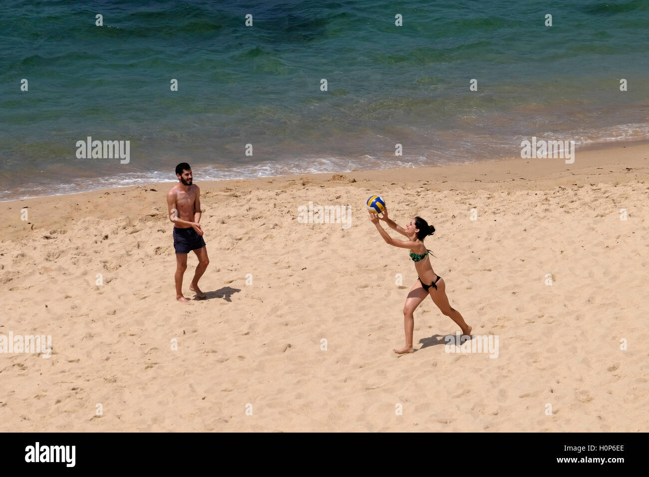 Overhead view of a young man and woman playing volleyball on the beach near the ocean - Stock Image