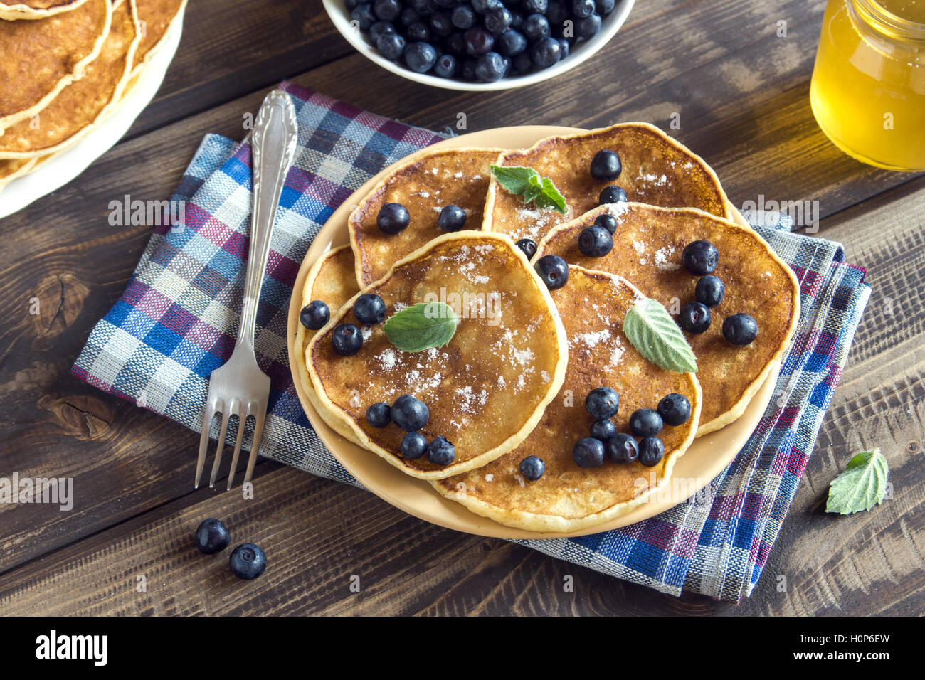 Pancakes on plate with blueberries, mint and honey for breakfast - homemade healthy vegetarian food Stock Photo