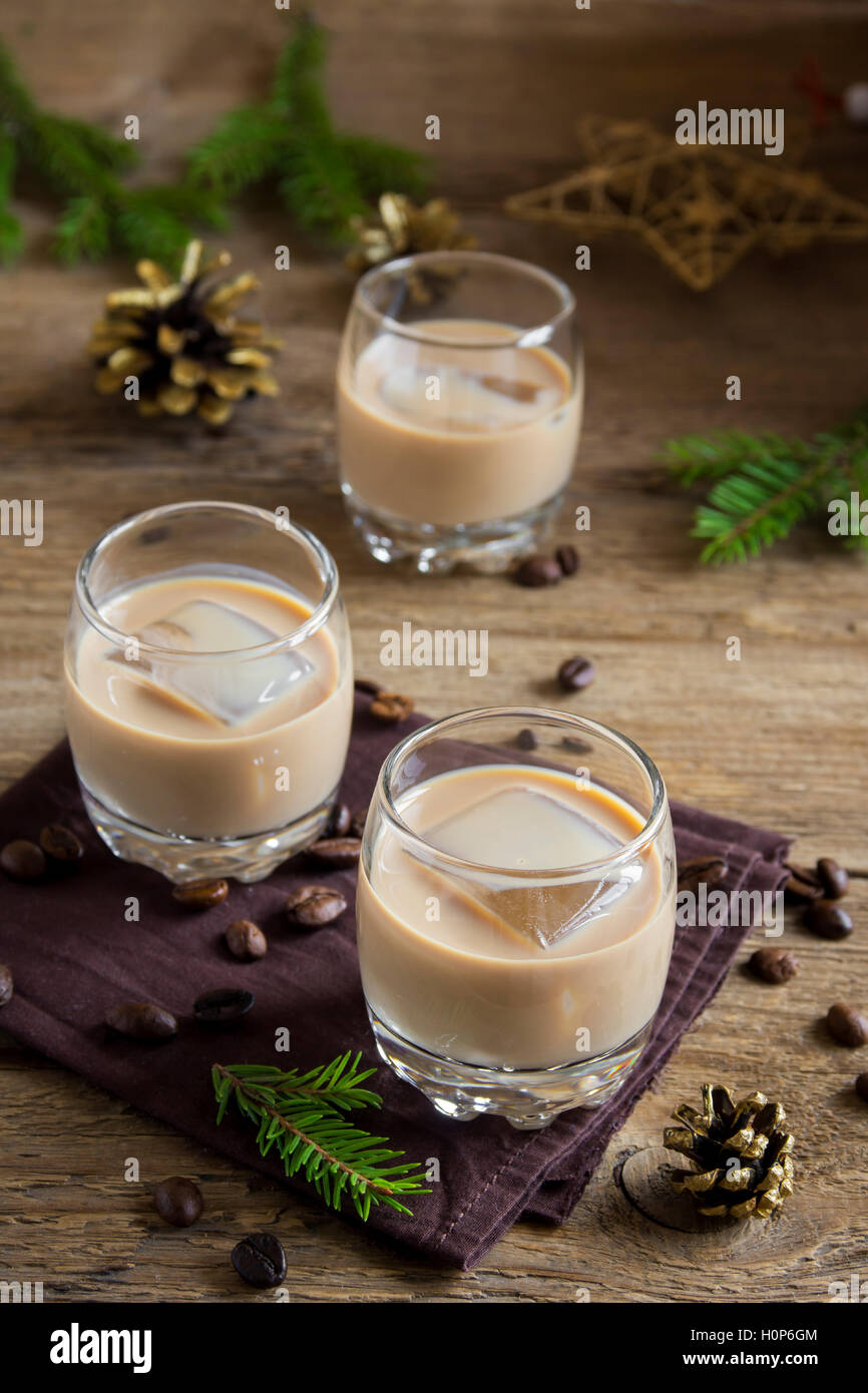 Irish cream coffee liqueur with ice, Christmas decoration and ornaments over rustic wooden background - homemade festive drink Stock Photo