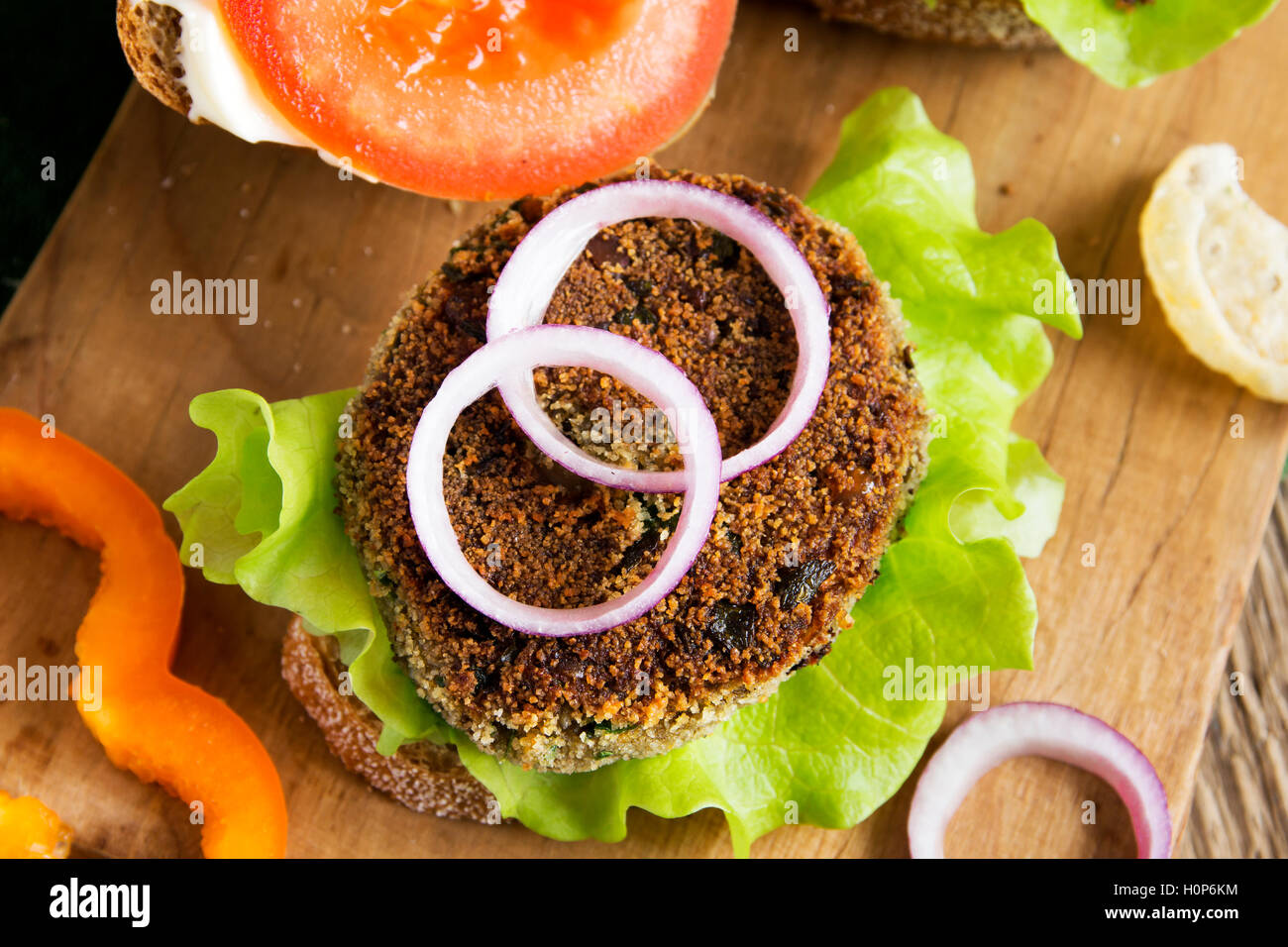 Vegetarian lentil burger with vegetables on wooden cutting board - healthy tasty vegetarian snack (food, lunch) - Stock Image