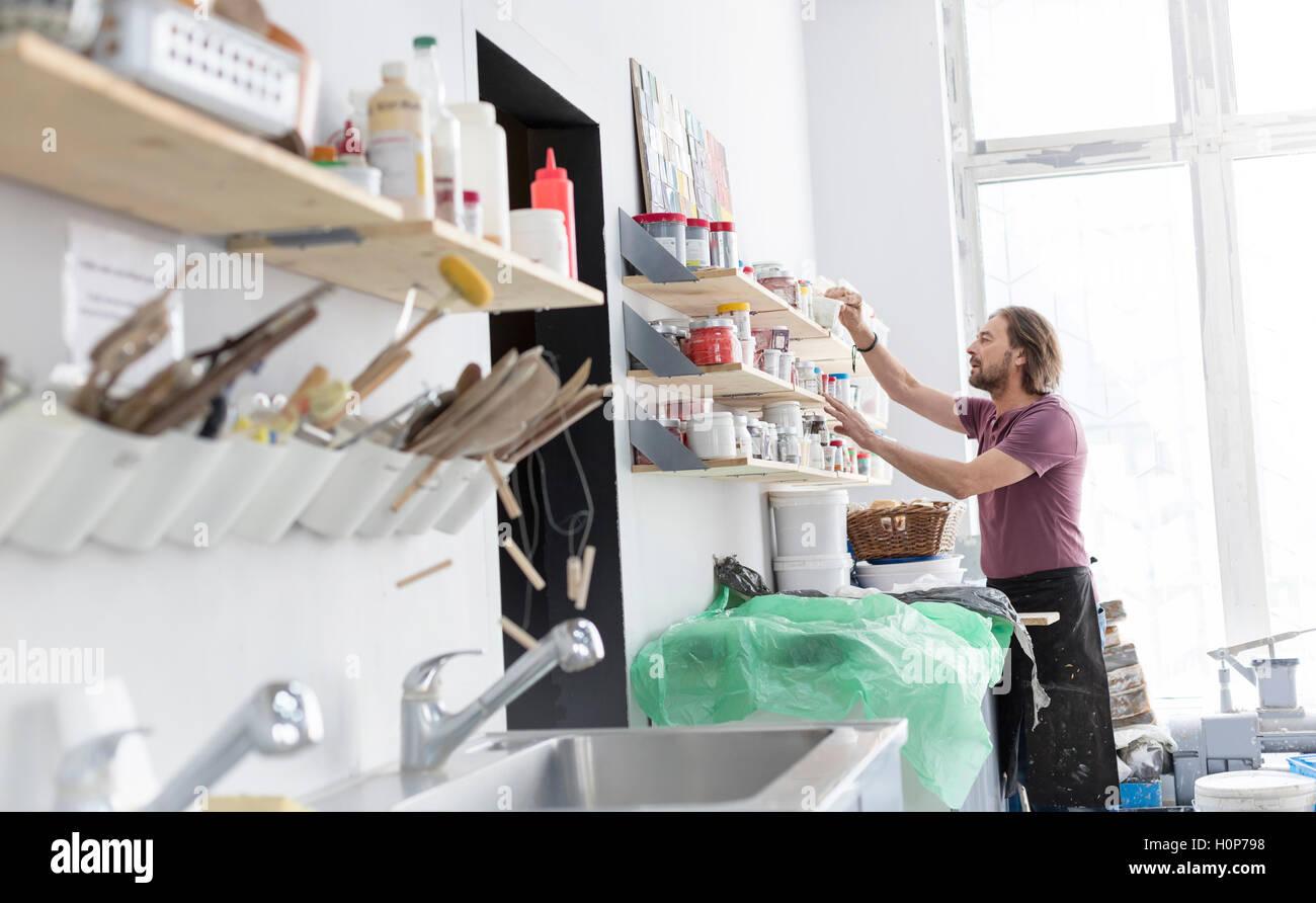 man browsing art supply shelf pottery studio - Stock Image