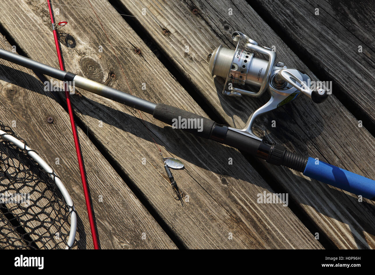 Fishing rod, reel, and net on a wooden landing beside a Vermont lake - Stock Image