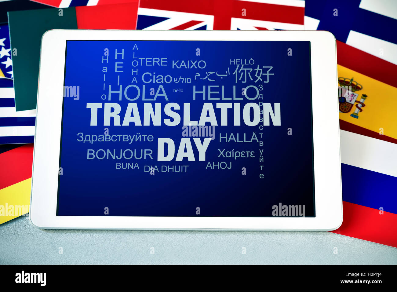 the text Translation Day in the screen of a tablet computer, and the word hello in different languages, surrounded - Stock Image