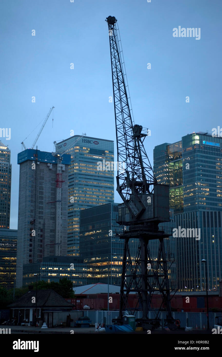 Evening view of the London Docklands area with old crane in foreground - Stock Image