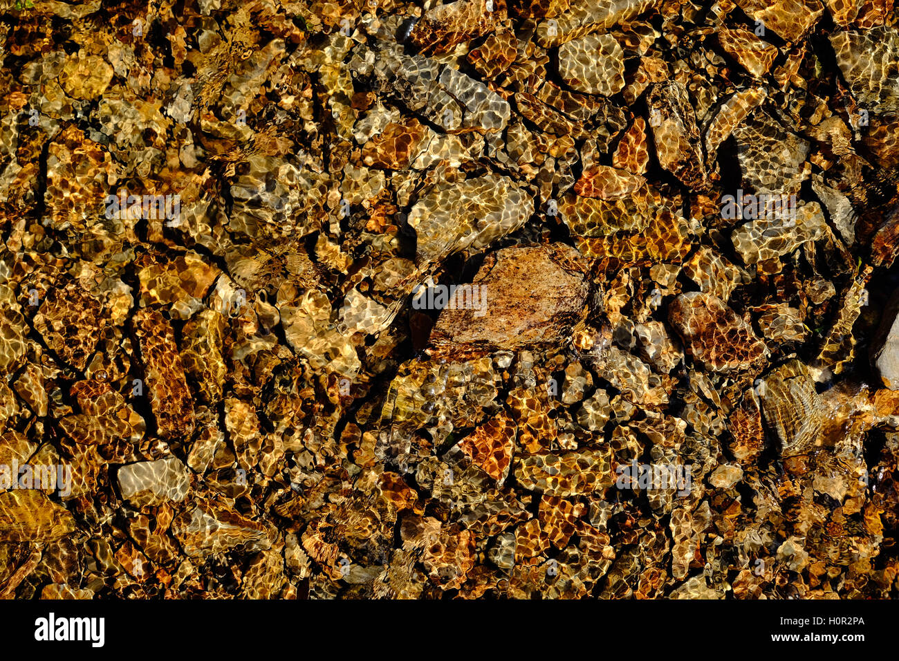 Clear rippled water from a stream over yellow rocks - Stock Image