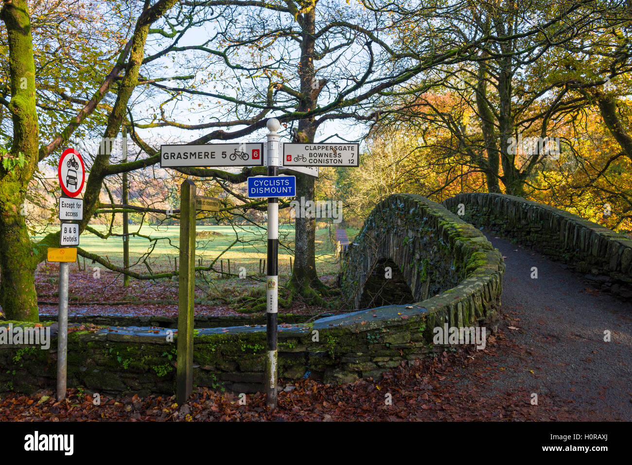 Footbridge over the River Rothay at Ambleside and signposts for the cycle path. Lake District National Park. Cumbria. - Stock Image