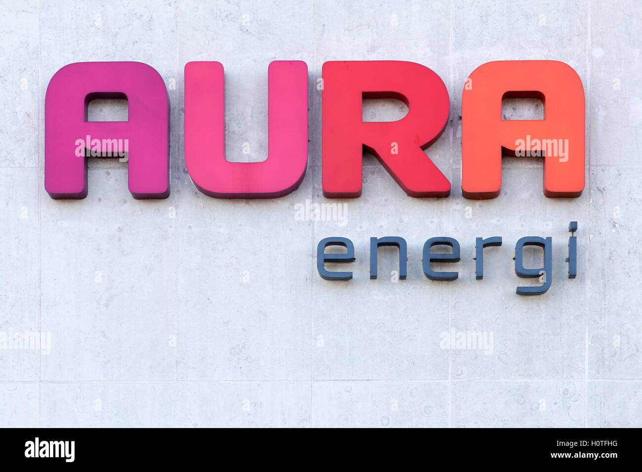 Aura Energi logo on a wall. Aura Energi provides electricity, energy, fiber, televisions and home appliances in - Stock Image
