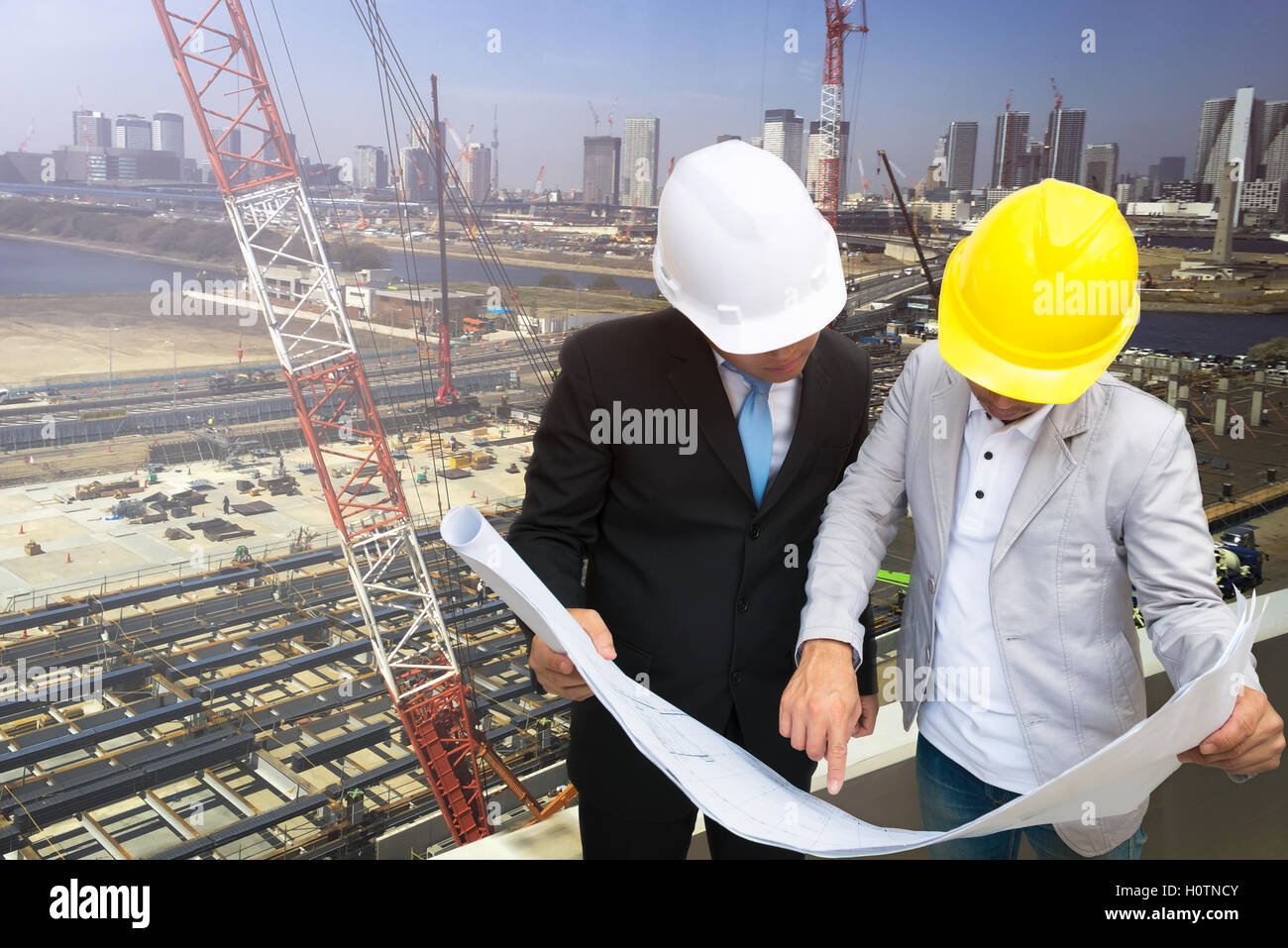 Management consulting with engineers working and holding blueprint management consulting with engineers working and holding blueprint engineer designer with helmet holding blueprint in his hand f malvernweather Choice Image