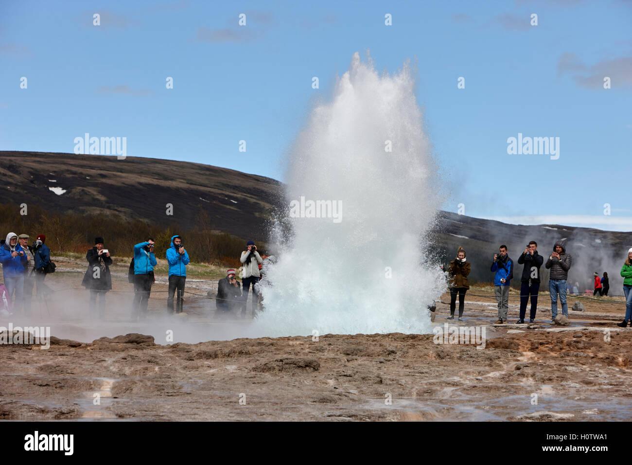 tourists stand around watching the strokkur geyser to erupt geysir Iceland Stock Photo