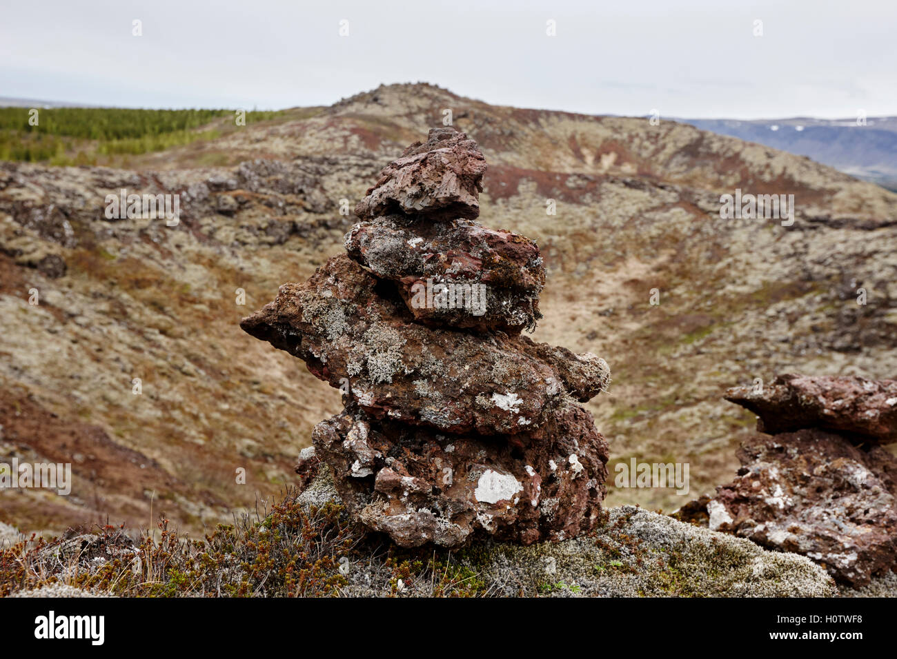 artificial pile of volcanic rocks created by tourists on edge of kerid volcano rim and caldera Iceland - Stock Image