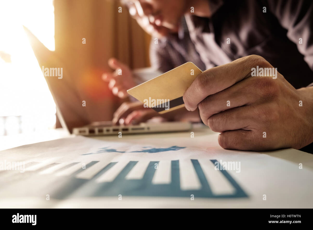 Business man hands using laptop and holding credit card with digital layer effect diagram as Online shopping concept - Stock Image
